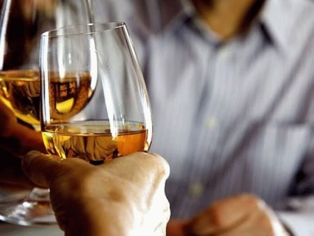 бокалы со спиртным на фоне мужчины в рубашке