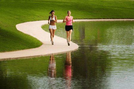 девушки бегают по дорожке возле водоема