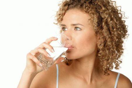 девушка пьет воду со стакана