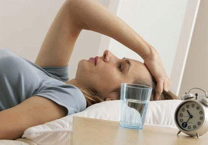 женщина лежит на постели рядом со стаканом воды