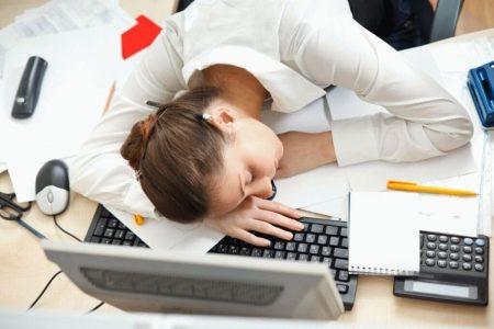 девушка спит за столом на бумагах и ноутбуке