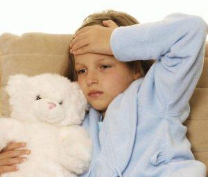 девочка с головной болью обнимает плюшевого мишку