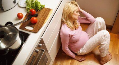 беременная сидит на полу возле стола