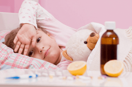 ребенок в постеле и рукой возле лба
