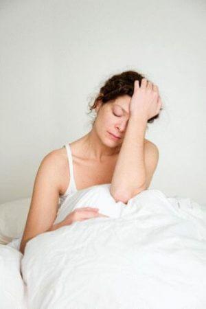 женщина после сна держится за голову сидя в постели