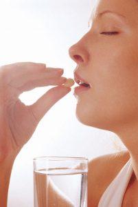 девушка с закрытыми глазами держит таблетку