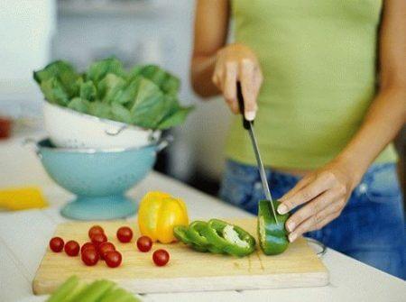 Женщина на кухне нарезает овощи