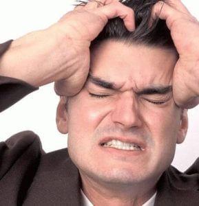 Мужчина с выражением боли на лице держится руками за голову