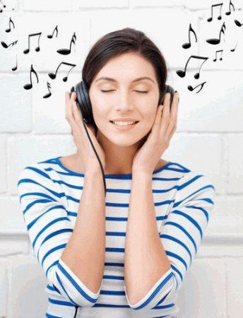 девушка в футболке в полосочку слушает музыку в наушниках
