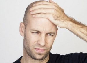 Мужчина держится ладонью за голову