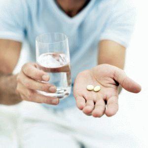 Мужчина протягивает стакан с водой и таблетки