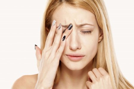 молодая девушка держится кончиками пальцев в области правого глаза