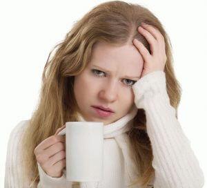 Девушка в белом свитере держит в одной руке чашку, другой держится за голову