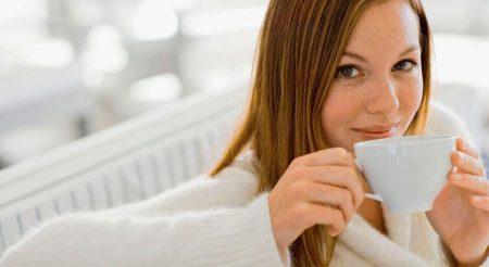 Девушка пьет чай с белой чашки
