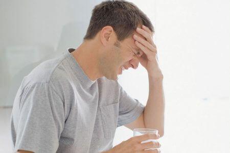 мужчина в футболке со стаканом в руке держится за лоб