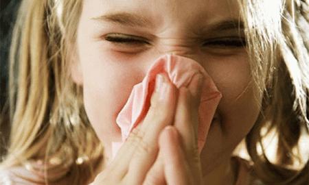 девочка выдувает сопли из носа в салфетку