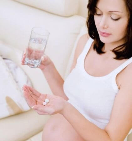 Женщина держит в руке таблетки