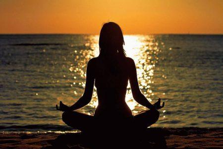 девушка возле моря вовремя заката в позе лотоса