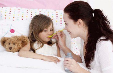 мама дает лекарство с ложечки дочери