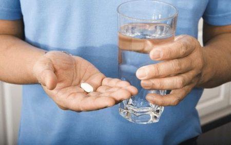 мужчина в белой футболке держит стакан с водой и таблетку в ладони