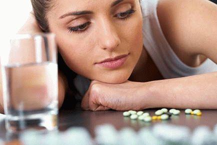 Девушка смотрит на рассыпаные по столу таблетки