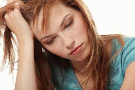 девушка с грустным лицом положила голову на ладонь