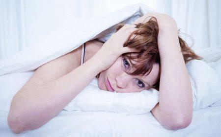 девушка лежит под одеялом на кровати держась руками за голову