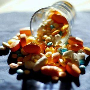 прозрачный стакан с разнообразными таблетками и пилюлями
