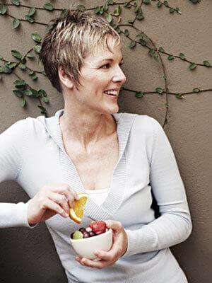 Женщина держит в руках пиалу с фруктами