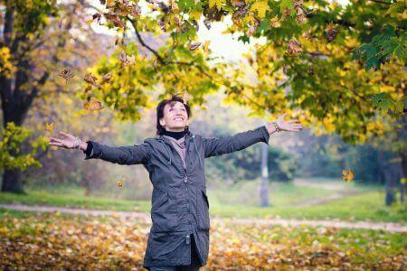 девушка подкидывает вверх желтые листья