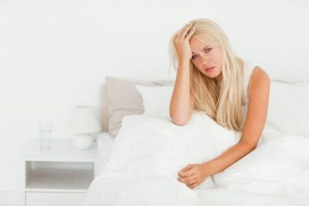 девушка сидит на кровати держась за голову