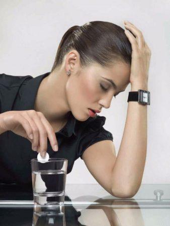 девушка кладет таблетку в стакан с водой