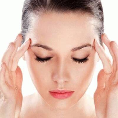 Женщина делает себе массаж головы