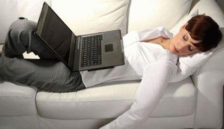 девушка спит на диване с ноутбуком на животе