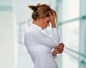 Женщина в белой рубашке держится за лоб