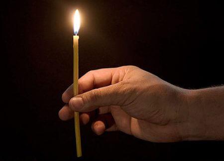 зажженная свеча в правой руке