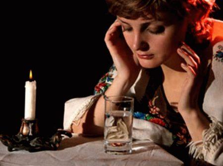 девушка в национальном костюме сидит за столом перед стаканом с водой и свечей