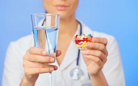 пилюли и таблетки в стаканчике в одной руке и стакан води в другой руке у доктора