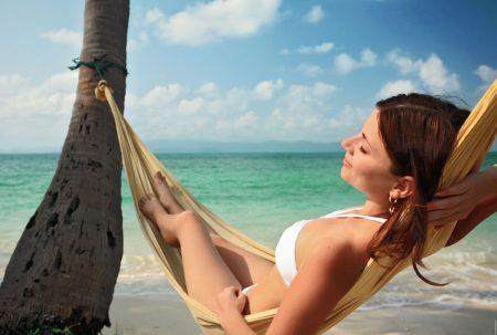 Женщина отдыхает в гамаке на берегу моря