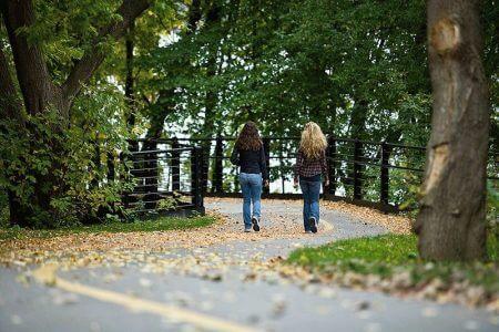 две девушки гуляют по дороге в парке