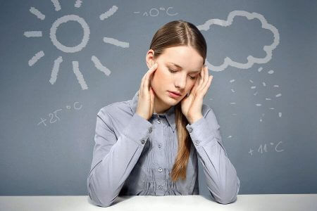 Девушка в серой блузе за столом на фоне графического изображения погодных условий