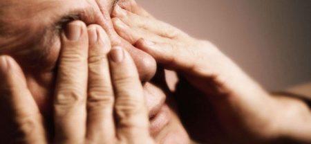 мужчина закрыл глаза пальцами рук