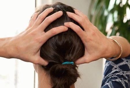 женщина держится обеими руками за голову