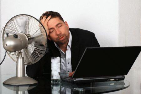 Мужчина сидит за столом возле вентилятора