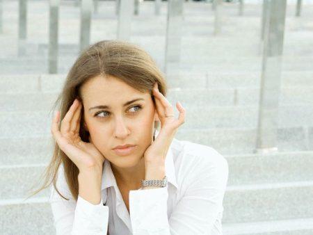 Девушка в белой рубашке держится пальцами рук в области висков