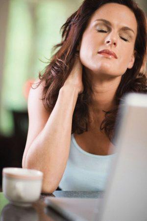 девушка за компьютером держится за затылок