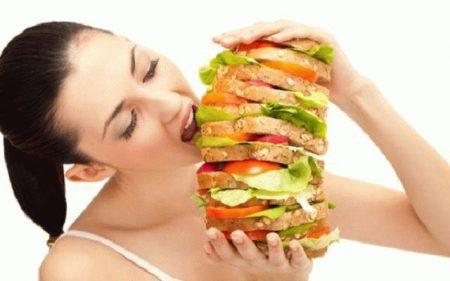женщина ест очень большой бутерброд
