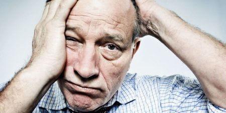 пожилой мужчина держится обеими руками за голову