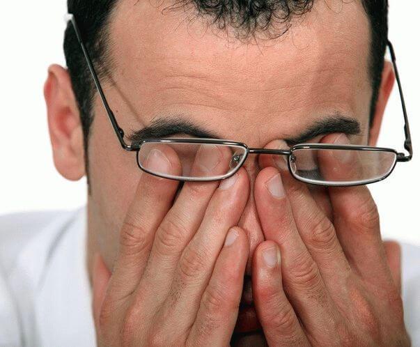 Мужчина пальцами трет глаза под очками