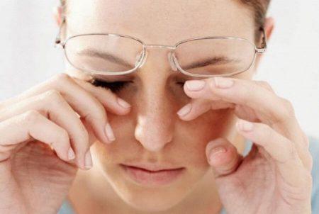 Девушка кончиками пальцев трет глаза под очками